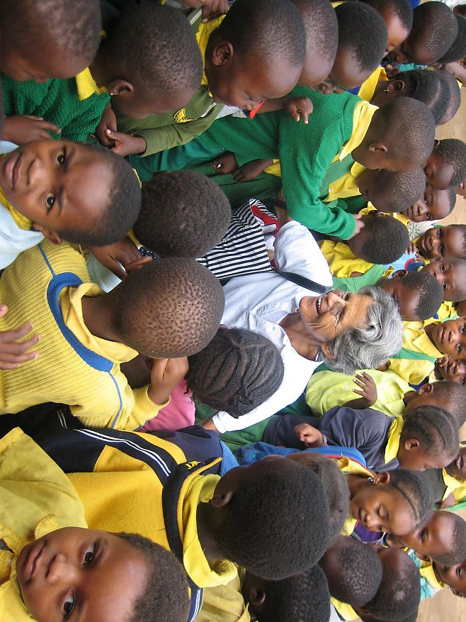 Truus van Hout surrounded by school children of Tanzania